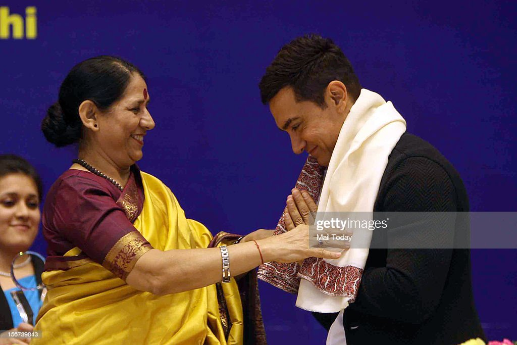 Minister for women child development Krishna Tirath felicitates actor Aamir Khan during the launch the IEC Campaign against Malnutrition in New Delhi on Monday.