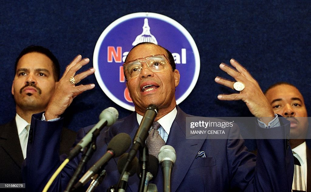 Minister Louis Farrakhan (C) of the Nation of Islam speaks to reporters 14 July, 2000 during a press conference at the National Press Club in Washington, DC. Farrakhan is calling for one million families to assemble on the National Mall in Washington, DC 16 October to observe the fifth anniversary of the Million Man March and to endorse the 'Redeem the Dream March on Washington' event. Men at rear are unidentified. AFP PHOTO/Manny CENETA
