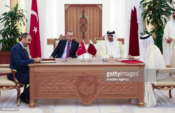 Minister of Justice of Turkey Abdulhamit Gul signs an agreement on behalf of Turkey as he is flanked by President of Turkey Recep Tayyip Erdogan and...