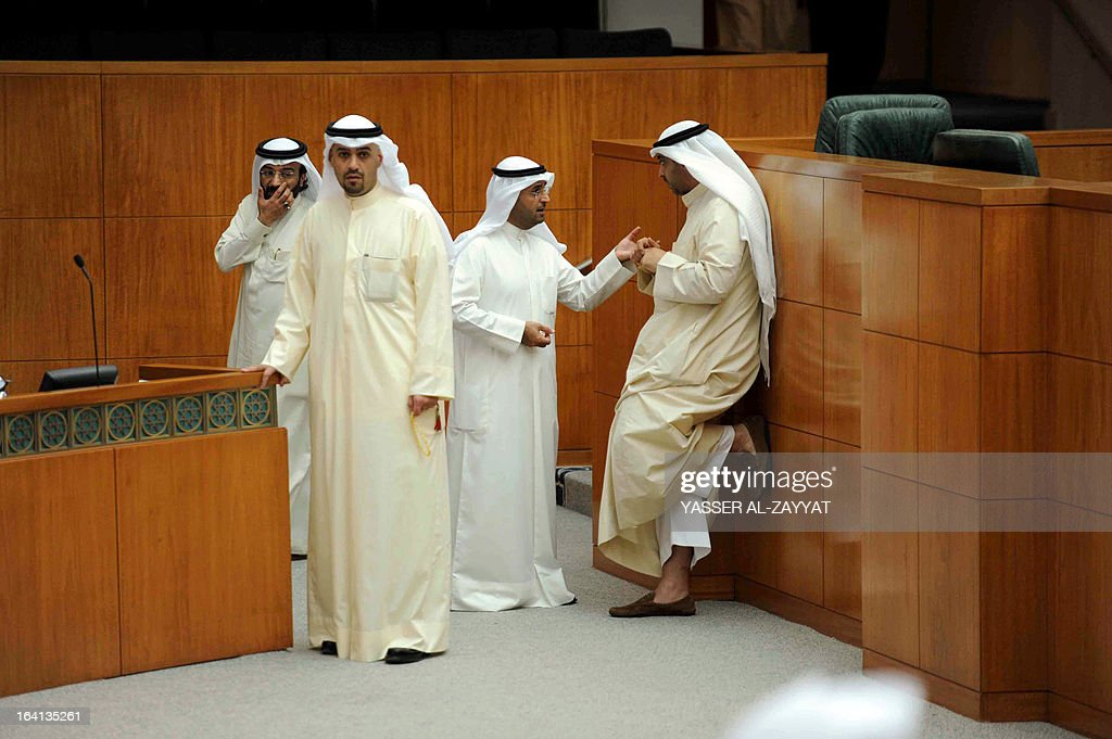 Minister of State for Municipality Affairs Sheikh Mohammed al-Abdullah al-Sabah speaks with Minister of Education Nayef al-Hajraf as Minister of Commerce and Industry Anas al-Saleh and MP Esam al-Dabous look on during a parliament session at Kuwait national assembly in Kuwait City on March 20,2013. Kuwait's parliament passed in principle a bill that requires the government to buy billions of dollars of bank loans owed by citizens and reschedule them after waiving interest.