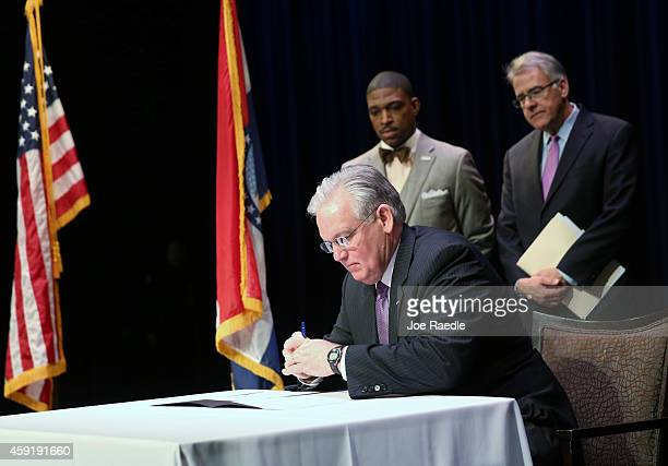 Minister Starsky Wilson and businessman Richard McClure stand behind Missouri Governor Jay Nixon as he signs an executive order establishing a...