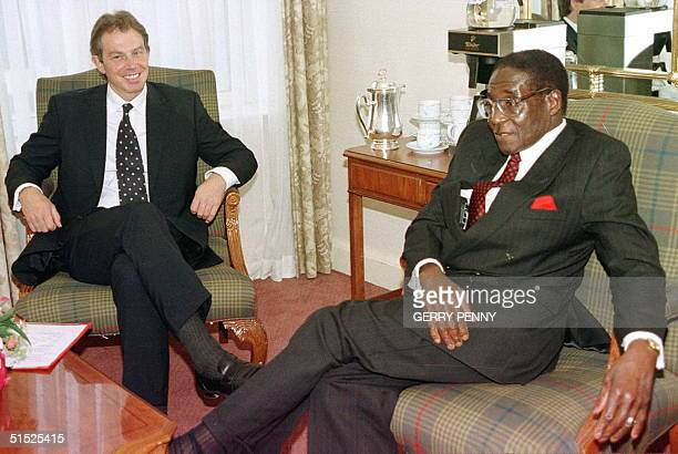 Minister Tony Blair chats with President Robert Mugabe of Zimbabwe 24 October in Edinburgh before the start of the Commonwealth Heads of Government...