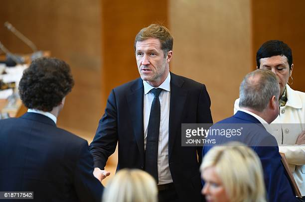 MinisterPresident of Belgium's Frenchspeaking Walloon Region Paul Magnette shakes hands with members of Parliament as he arrives for a debate about...