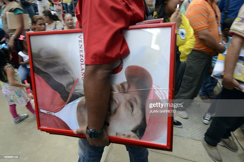 A Ministry for the Revolutionary Transformation of Greater Caracas staffer carries a portrait of Venezuelan President Hugo Chavez before a ceremony to deliver government-built flats to their new owners, in Caracas on February 7, 2013. AFP PHOTO/Juan Barreto