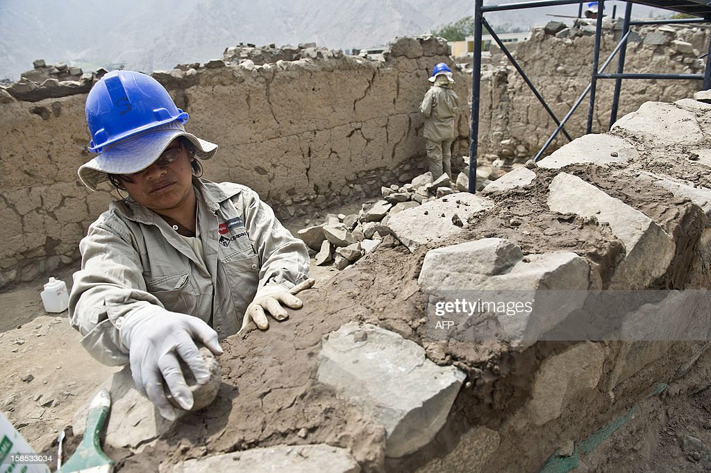 Ministry of Culture workers restore part of a wall of the Huaycan de Cieneguilla archaeological site, in Cieneguilla, 70 km east from Lima on December 12, 2012. A group of archaeologists have been working for five years in the recovery and preservation of the site. AFP PHOTO/ ERNESTO BENAVIDES