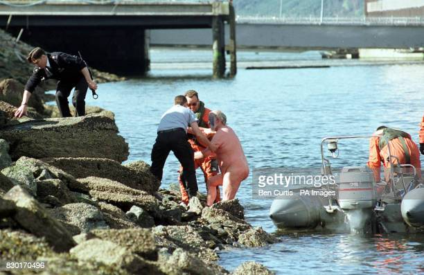 Ministry of Defence personnel escort an antinuclear protester from Faslane Peace Camp out of Loch Long after he attempted to swim to the final...