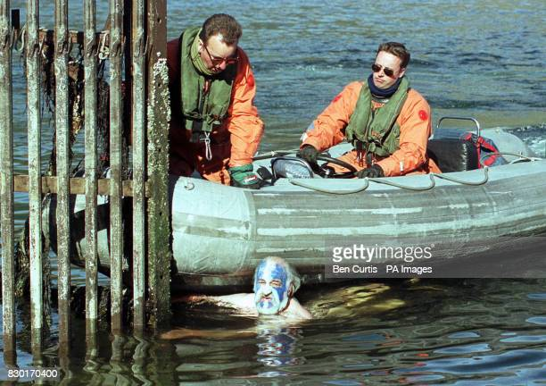 Ministry of Defence personnel try to stop an antinuclear protester from Faslane Peace Camp trying to swim out into Loch Long to disrupt the arrival...