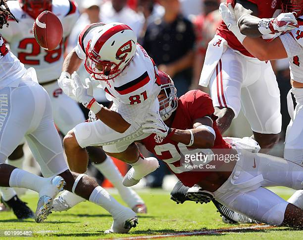 Minkah Fitzpatrick of the Alabama Crimson Tide forces a fumble by Kylen Towner of the Western Kentucky Hilltoppers during the opening kickoff at...