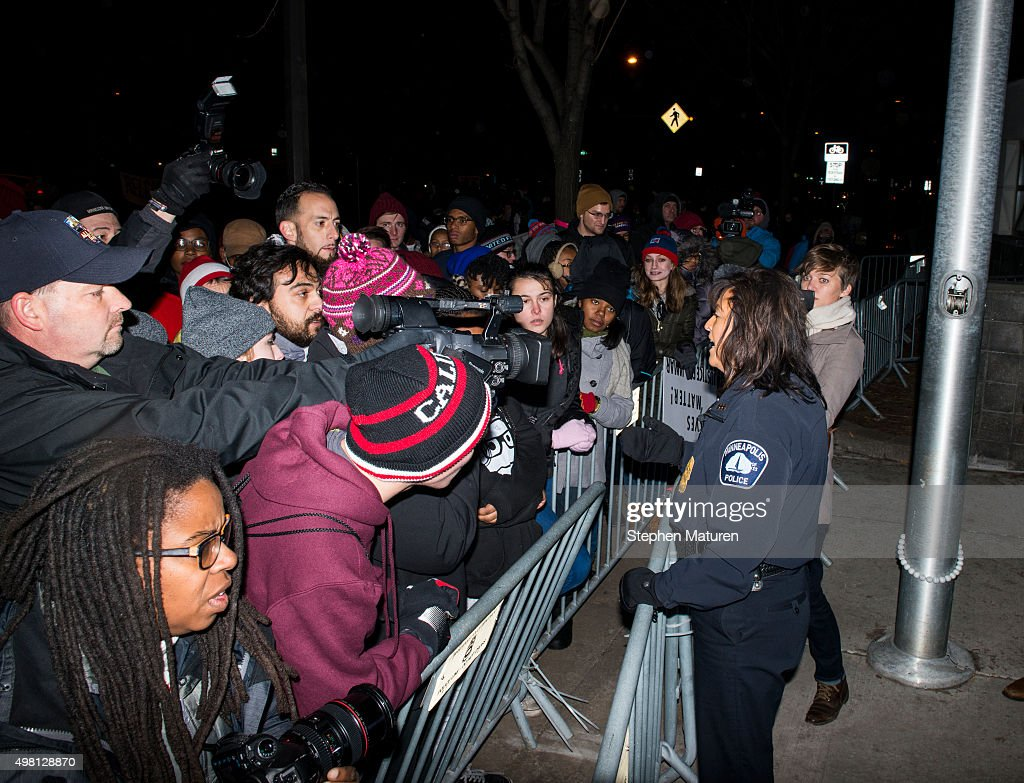 Minneapolis Police Chief Janee Harteau right speaks with media and protestors separated by a barricade outside the 4th Precinct police station...