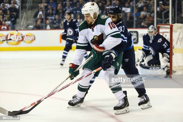 Minnesoda Wild forward Chris Stewart tries to skate away from Winnipeg Jets defenseman Dustin Byfuglien during the NHL game between the Winnipeg Jets...