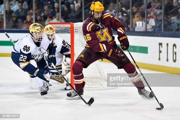 Minnesota Golden Gophers forward Jack Ramsey tries to get a shot off on Notre Dame Fighting Irish defenseman Andrew Peeke during the game between the...