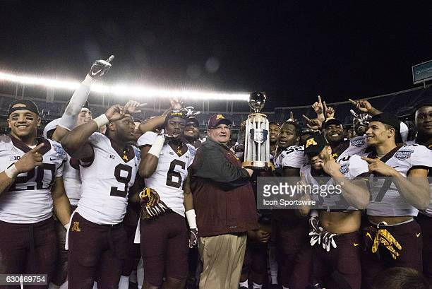 Minnesota head coach Tracy Claeys accepts the Holiday Bowl Trophy with his team after the National Funding Holiday Bowl football game between the...