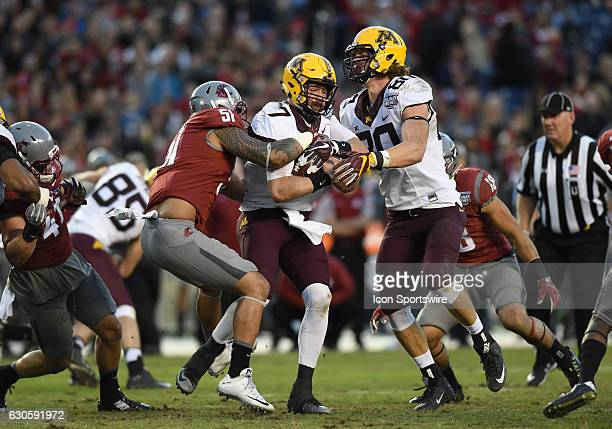 Minnesota Mitch Leidner runs the ball and is stopped by Washington State Frankie Luvu during the National Funding Holiday Bowl game between the...