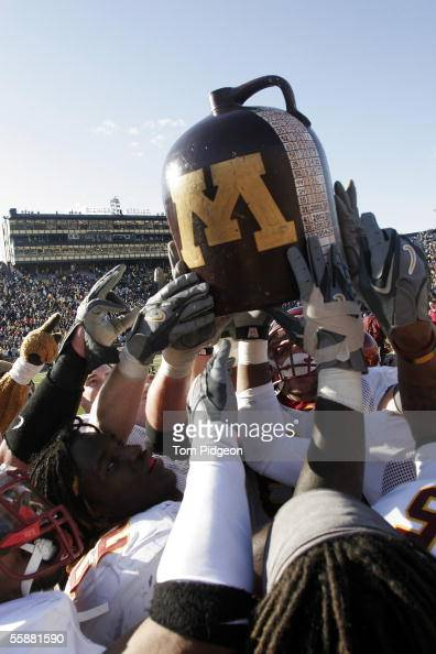 Minnesota players celebrate with the 'Little Brown Jug' trophy after defeating Michigan at Michigan Stadium October 8 2005 in Ann Arbor Michigan...