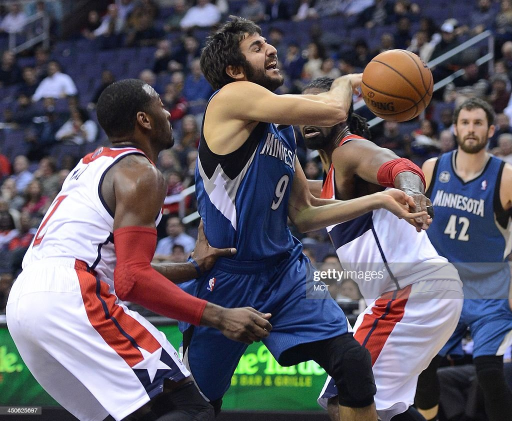 Minnesota Timberwolves point guard Ricky Rubio (9) gets fouled by Washington Wizards point guard John Wall (2), as he drives the lane between Wall and Wizards power forward Nene Hilario (42), right, in the second quarter at the Verizon Center in Washington, Tue., Nov 19, 2013.