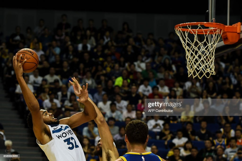 Minnesota Timberwolves's NBA player Karl-Anthony Towns (L) slam dunks during the NBA Basketball Game between Golden State Warriors and Minnesota Timberwolves in Shanghai on October 8, 2017. /