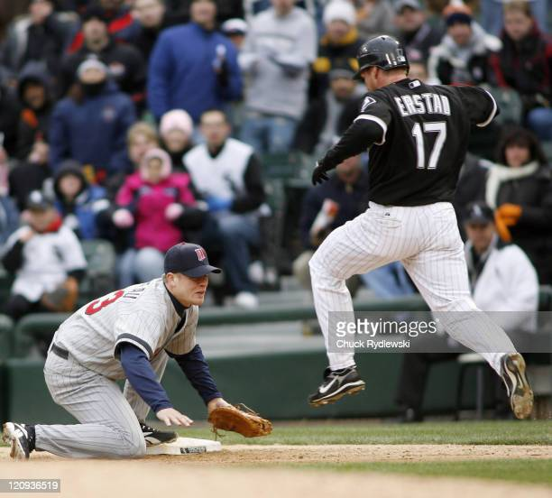 Minnesota Twins' 1st Baseman Justin Morneau tags 1st base just ahead of Darin Erstad during their game against the Chicago White Sox April 7 2007 at...