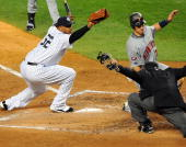 Minnesota Twins catcher Joe Mauer is safe at home scoring on a passed ball by New York Yankees catcher Jorge Posada in the third inning as New York...