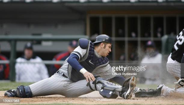 Minnesota Twins' Catcher Joe Mauer takes a late throw as Scott Podsednik slides safely into home plate during their game against the Chicago White...