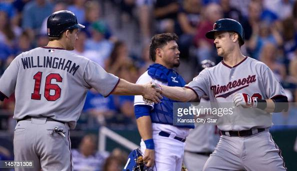 Minnesota Twins' Justin Morneau is congratulated by Josh Willingham after hitting a tworun homer in the fifth inning against the Kansas City Royals...