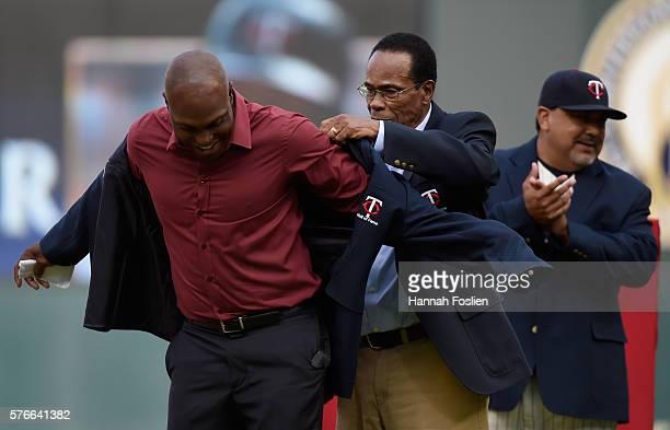 Minnesota Twins legend Rod Carew helps former Minnesota Twins player Torii Hunter into his jacket as bullpen coach Eddie Guardado looks on as Hunter...