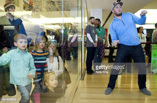 Minnesota Twins player Glen Perkins plays Kinect 'Rivals' Water ski game on the new Xbox One with customers at the Microsoft retail store while...