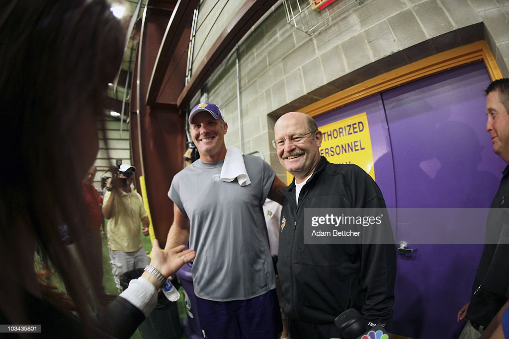 Minnesota Vikings quarterback Brett Favre talks with the media as head coach Brad Childress smiles following a press conference after the first morning practice since returning to Vikings Winter Park on August 18, 2010 in Eden Prairie, Minnesota. Favre injured his ankle last year and had been reportedly considering retiring after one season with the Vikings.
