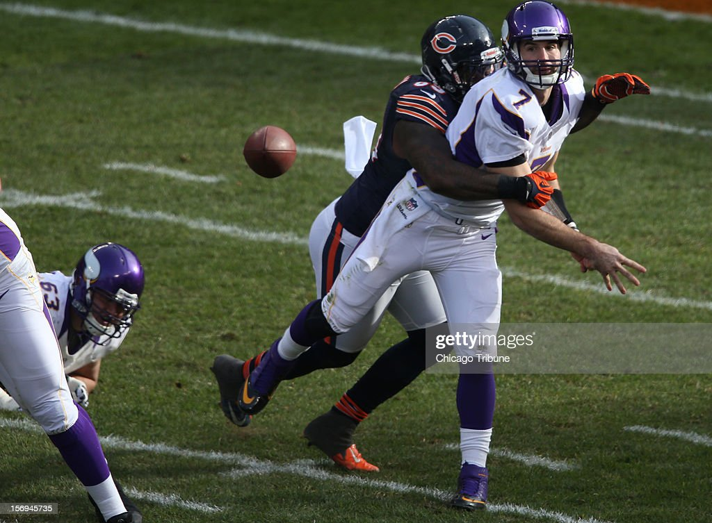 Minnesota Vikings quarterback Christian Ponder (7) throws for a 1st down while being wrapped up by Chicago Bears defensive tackle Henry Melton (69) in the 2nd quarter at Solider Field on Sunday, November 25, 2012, in Chicago, Illinois. The Bears defeated the Vikings, 28-10.