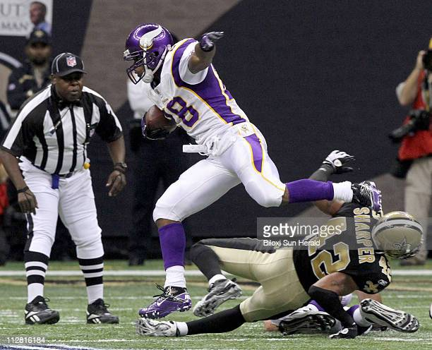 Minnesota Vikings running back Adrian Peterson leaps over New Orleans Saints defender Darren Sharper during firstquarter action in the NFC...