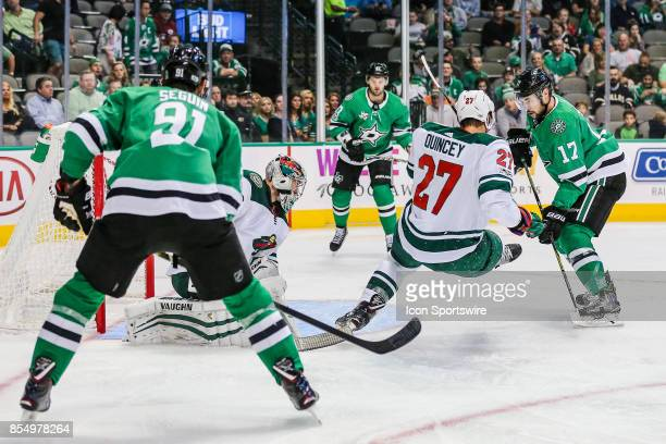 Minnesota Wild defenseman Kyle Quincey gets tripped up in front of the net as Dallas Stars center Tyler Seguin and center Devin Shore crash towards...