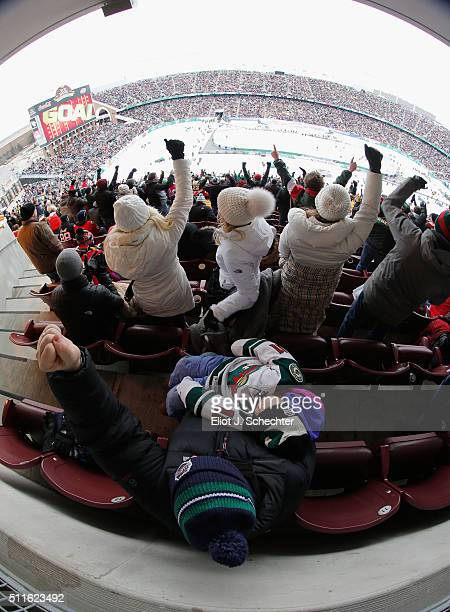 Minnesota Wild fan cheers as he holds his sleeping son after a goal by Jason Pominville of the Minnesota Wild against the Chicago Blackhawks in the...