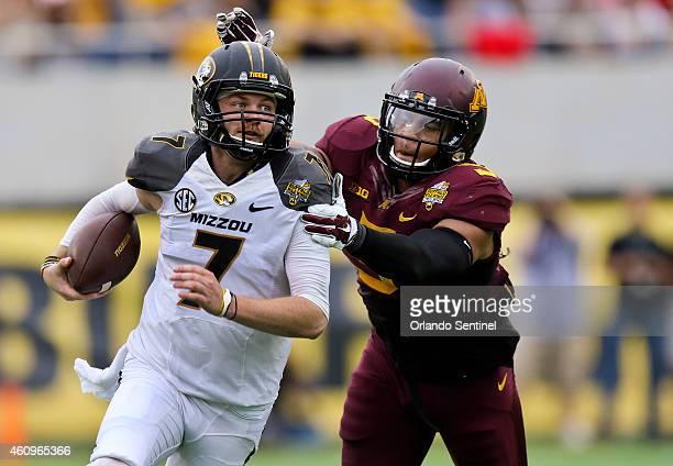 Minnesota's Damien Wilson tries to bring down Missouri quarterback Maty Mauk during a keeper run the Buffalo Wild Wings Citrus Bowl at Citrus Bowl...