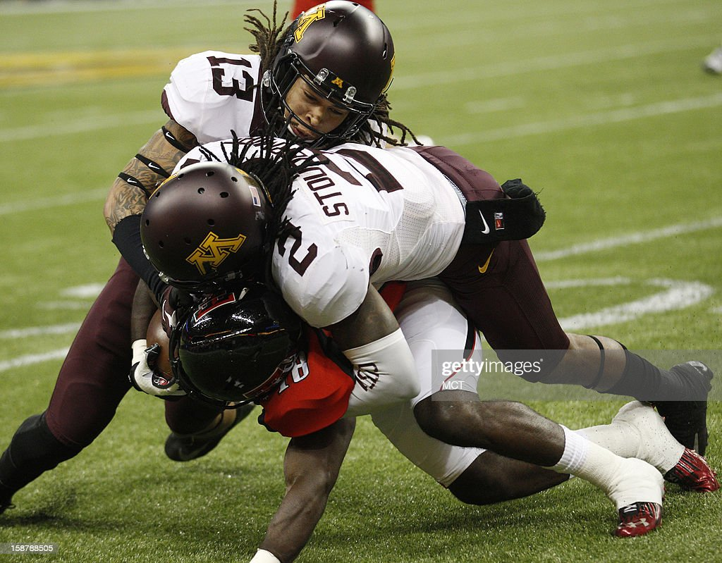 Minnesota's Derrick Wells and Troy Stoudermire wrap up Texas Tech's Eric Ward during the first quarter of the Meineke Car Care Bowl of Texas on Friday, December 28, 2012, at Reliant Stadium in Houston, Texas.