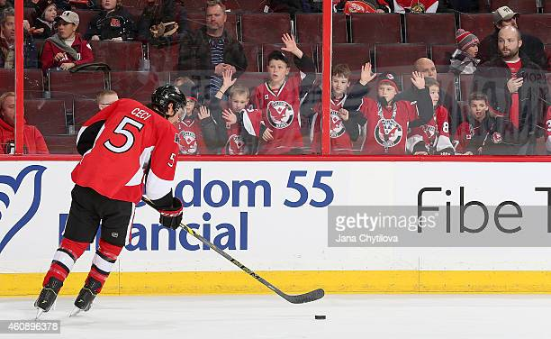 Minor hockey kids try to get the attention of Cody Ceci of the Ottawa Senators as he skates by during warmups prior to an NHL game against the...