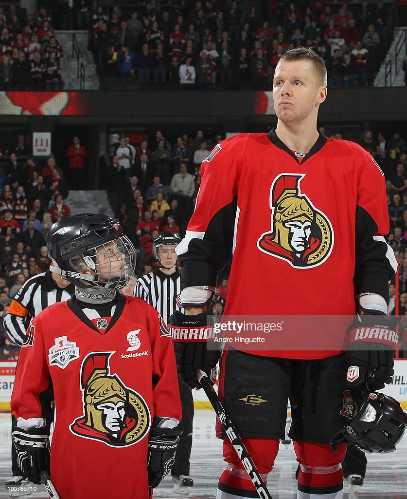 A minor hockey player partaking in pre-game ceremonies looks up at Marc Methot #3 of the Ottawa Senators during the singing of the national anthems prior to a game against the Buffalo Sabres on February 5, 2013 at Scotiabank Place in Ottawa, Ontario, Canada.