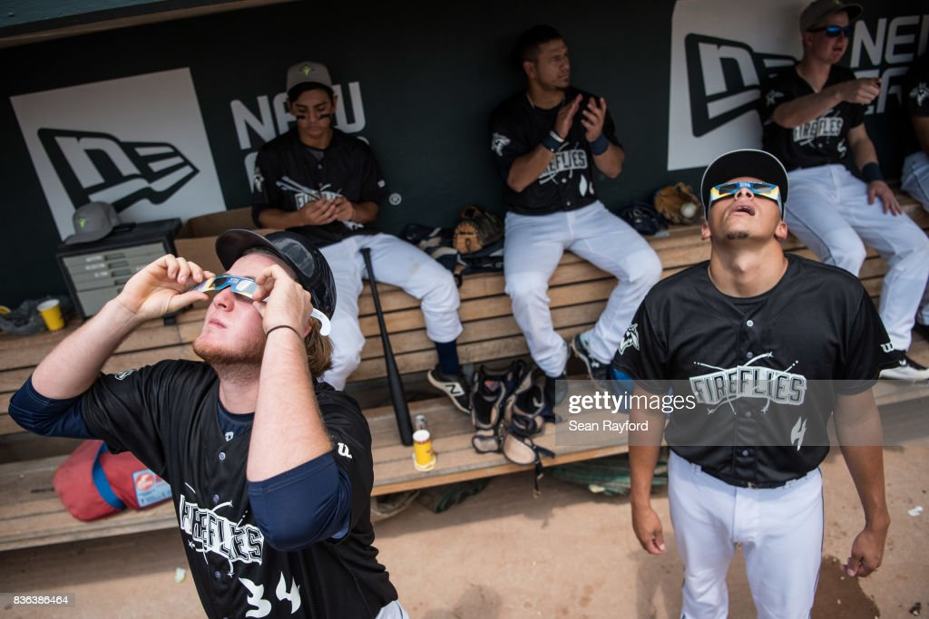 Minor league baseball players Dash Winningham (34) and Justin Brantley (4), with the Columbia Fireflies, watch a solar eclipse at Spirit Communications Park August 21, 2017 in Columbia, South Carolina. The astrological occurrence marked the first transcontinental total solar eclipse in 99 years.