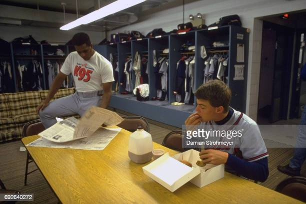 Richmond Braves Pedro Borbon reading newspaper and Chipper Jones eating in locker room before game vs Syracuse Chiefs at MacArthur Stadium Syracuse...
