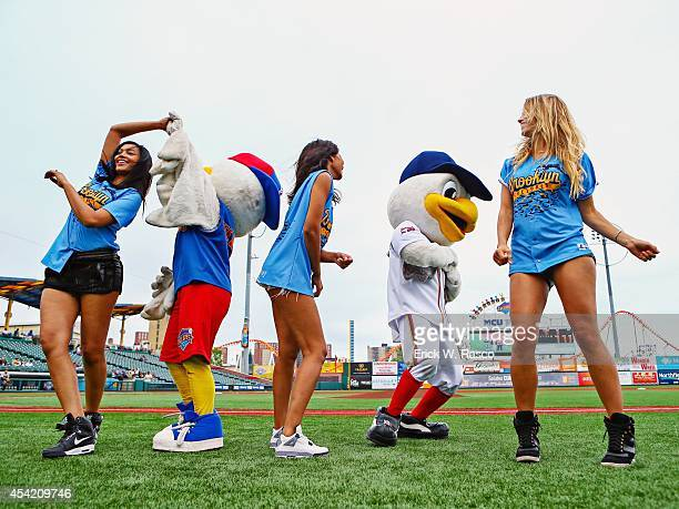Sports Illustrated swimsuit models Ariel Meredith Chanel Iman and Hannah Ferguson dancing on field with mascots Sandy the Seagull and PeeWee before...