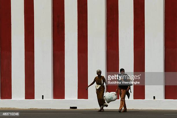 Minority ethnic Tamil women walk by the temple wall on August 122015 in Jaffna Sri Lanka The UN's Human Rights Council investigation into alleged war...