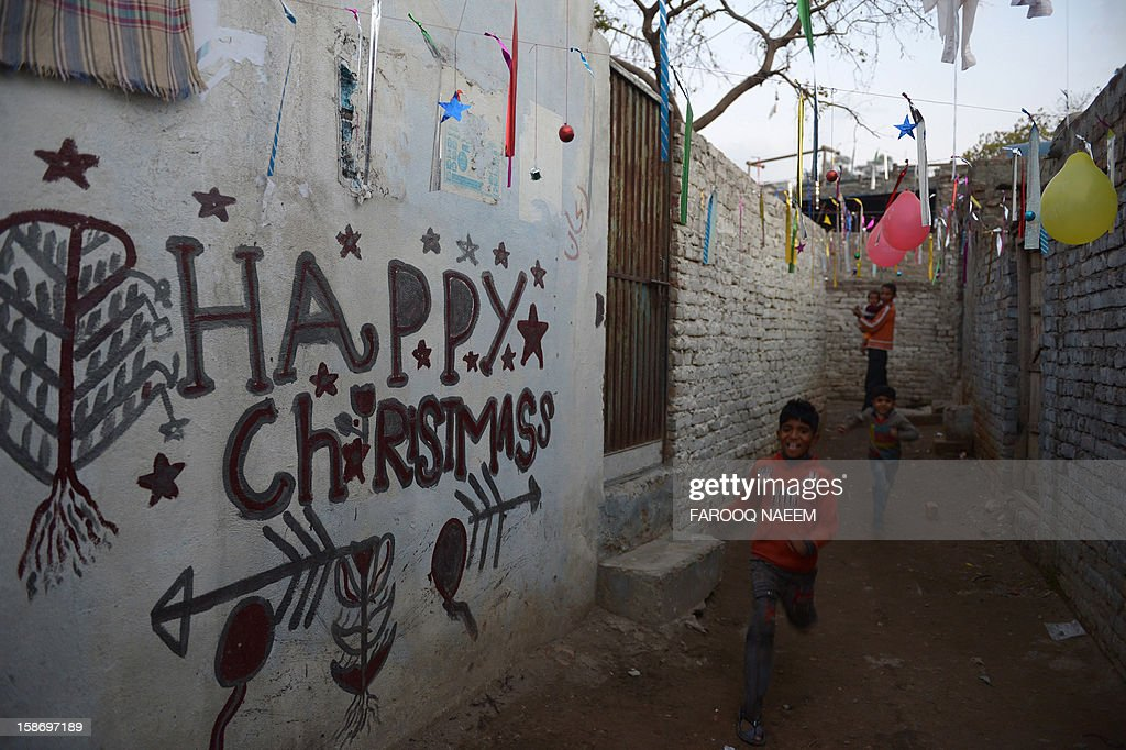 Minority Pakistani Christians walk on an alley past Christmas decorations in Islamabad on December 24, 2012. There is a tiny Christian minority in Pakistan, where only three percent of the population of 167 million are estimated to be non-Muslim. AFP PHOTO/Farooq NAEEM