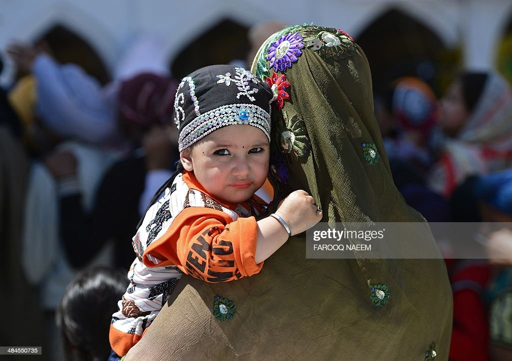 A Minority Pakistani Sikh devotee carries her child at the Gurdwara Punja Sahib in Hasan Abdal, the third most sacred city for the followers of the Sikh religion, on April 13, 2014. Around 2,500 Sikhs from India, 4,000 from Pakistan, and more than 200 from European and other countries are participating in the three-day Baisakhi festival. AFP PHOTO/Farooq NAEEM