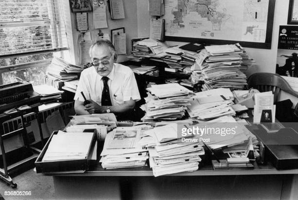 Minoru Yasui sits behind office desk piled high with papers *****he put in 2185 hours of overtime with no extra pay since he is an appointed official...