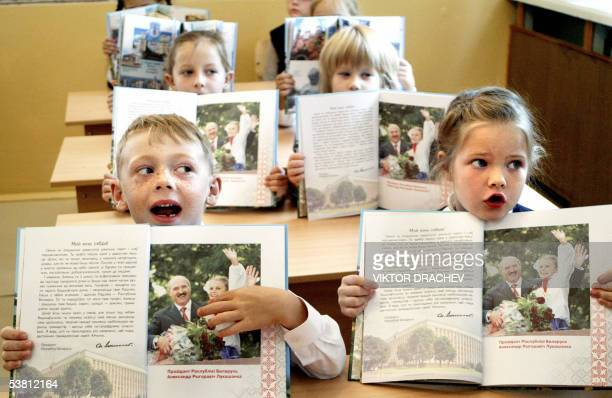 Belarus children sing the state anthem as they hold books with a portrait of Belarus President Alexander Lukashenko during the first lesson in a...