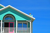 Bright beachfront home with mint siding and pink doors
