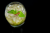 A Mint Julep, the official drink of the Kentucky Derby, with fresh mint leaves, crushed ice, and a red stir stick with a black background. Drink is oriented on the left side of the photo.