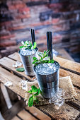 Mint julep cocktail alcoholic drink on wooden board in pub or restaurant.