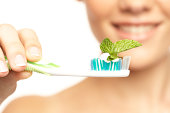Mint leaf on toothbrush, young woman smiling in background