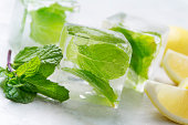 Mint infused ice cubes with lemon and mint garnish.