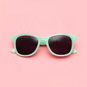Mint sunglasses isolated on pink background. Closeup. Square image.