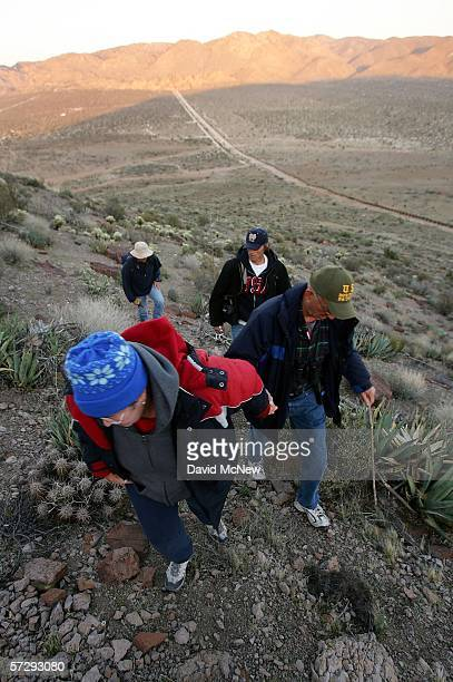 Minutemen Bea Mitchell Don Zaharee Steve Callagy and Matt Sandt climb a steep hill to their nighttime posts overlooking the border fence dividing the...